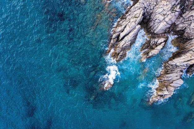 Vista aerea superiore della costa rocciosa con un mare cristallino