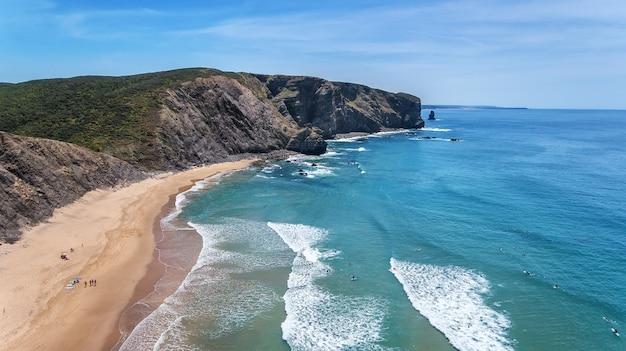 Aerea. surfisti di turisti sulla spiaggia di arrifana. algarve
