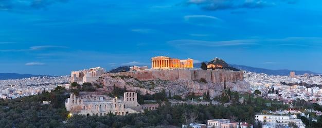 Vista aerea della collina dell'acropoli, coronata dal partenone, al di sopra dello skyline della città durante l'ora blu serale ad atene, grecia