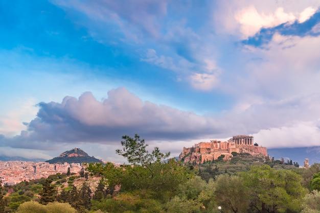 Vista aerea della collina dell'acropoli, coronata dal partenone e dal monte licabetto in serata ad atene, grecia