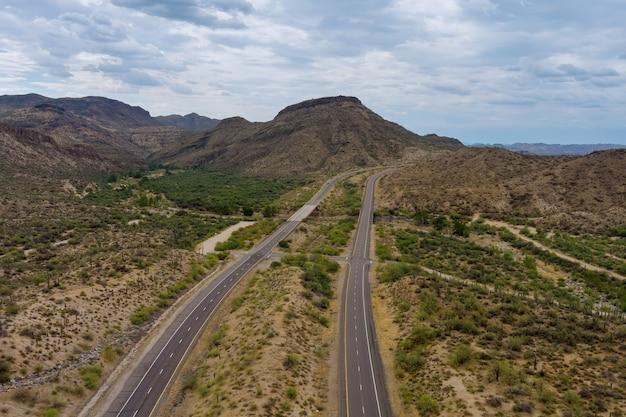 Avventura di vista aerea che viaggia sulla strada del deserto dell'autostrada asfaltata attraverso le montagne aride del deserto dell'arizona