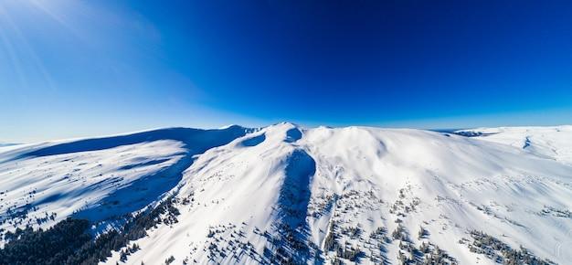 Vista aerea di un'incredibile vista ipnotizzante di un paesaggio invernale di montagna in una soleggiata giornata gelida in una stazione sciistica