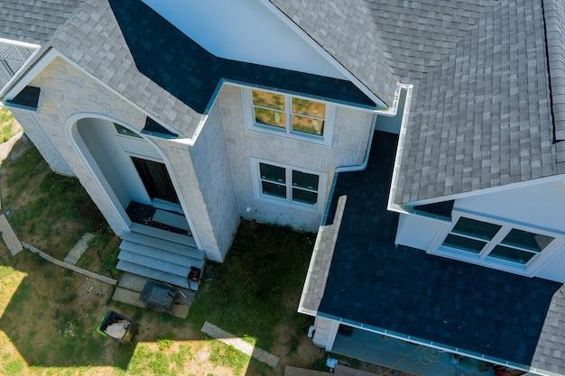 Vista aerea del cantiere di scandole di asfalto che copre la casa con una nuova finestra