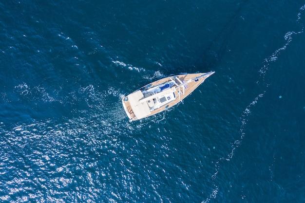 Vista aerea di un bellissimo yacht a vela bianco con una vela colorata.