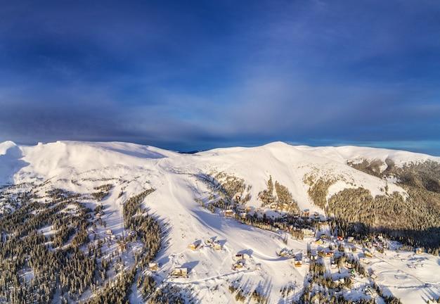 Vista aerea di bellissimi pendii montani invernali ricoperti di neve e bosco di abeti in una soleggiata giornata senza nuvole.