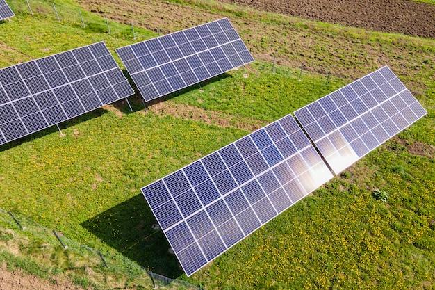 Vista aerea di pannelli solari fotovoltaici blu montati sul terreno del cortile per la produzione di elettricità ecologica pulita. produzione del concetto di energia rinnovabile.