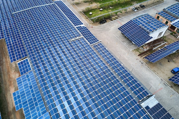 Vista aerea di pannelli solari fotovoltaici blu montati sul tetto di un edificio industriale per la produzione di elettricità ecologica verde. produzione del concetto di energia sostenibile.