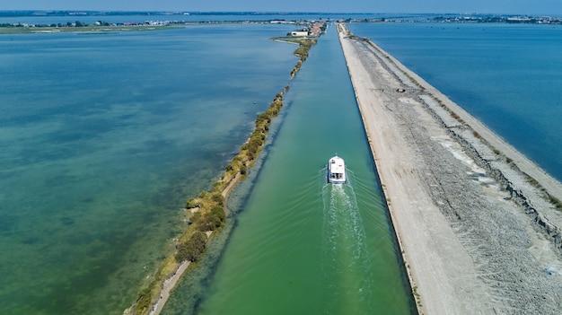 Vista aerea delle barche nel canale nella laguna del mar mediterraneo etang de thau acqua dall'alto, viaggio in chiatta nel sud della francia