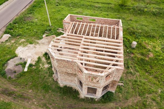 Vista aerea di una casa con mattoni a vista con la struttura di legno del soffitto in costruzione