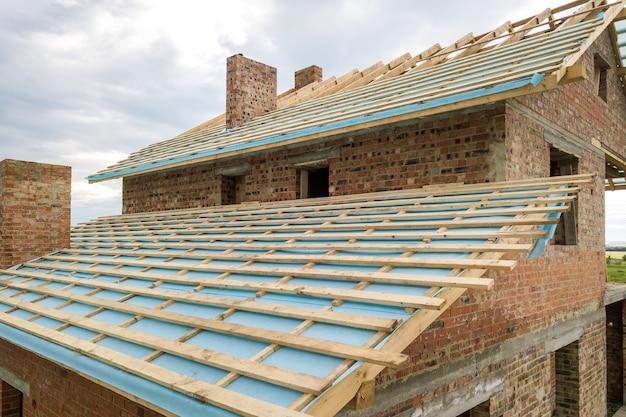 Vista aerea di una casa con mattoni a vista con struttura del tetto in legno in costruzione.