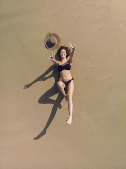 Vista aerea della donna castana che prende il sole sulla sabbia vicino al mare. indossa un bikini nero. è da sola. lei sta sorridendo. sta creando il simbolo della pace con le sue mani