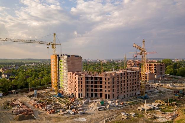 Vista aerea del cantiere. appartamento o edificio per uffici in costruzione. le gru a torre sul paesaggio del sobborgo e sul cielo blu copiano il fondo dello spazio.