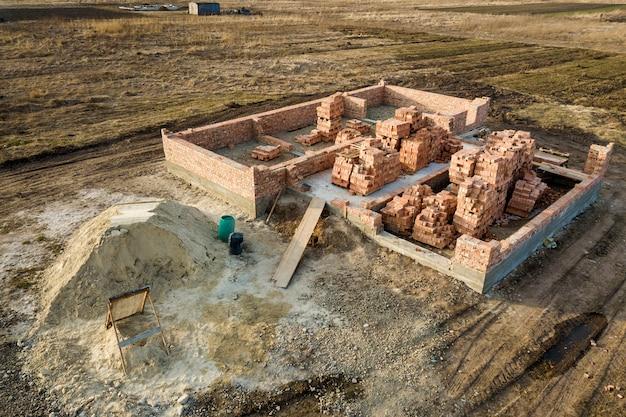 Vista aerea del cantiere. trincee scavate nel terreno e piene di cemento come base per la futura casa, pavimento del seminterrato in mattoni e pile di mattoni per la costruzione.