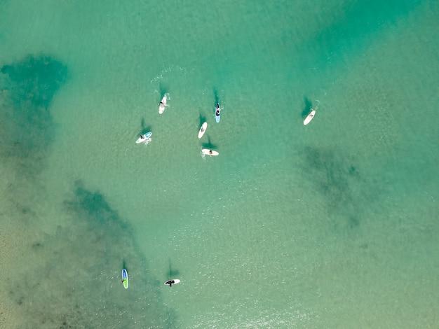 Vista aerea da drone di persone che praticano stand up paddle o sup nel mare limpido turchese del mediterraneo