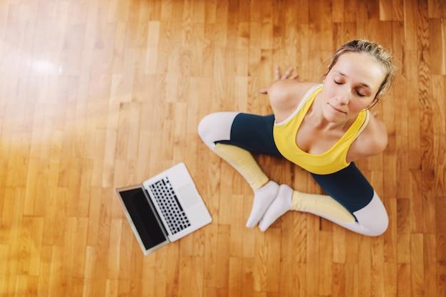 Vista aerea della donna calma che si siede nella posa di yoga del loto, meditando e seguendo la lezione in linea.
