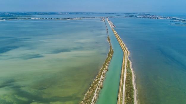 Vista aerea del canale in laguna dell'acqua di etang de thau del mar mediterraneo da sopra, la francia del sud