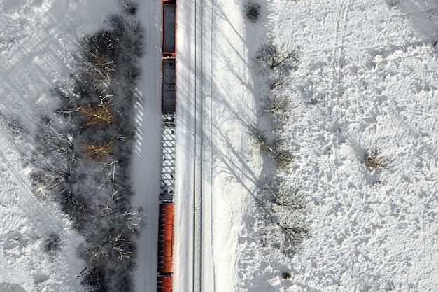 Vista aerea di vagoni cisterna del treno merci su rotaia a doppio binario con neve bianca nella vista dall'alto di inverno