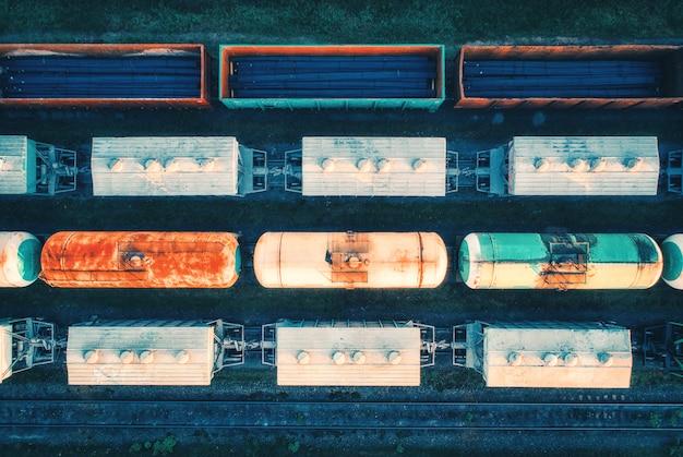 Vista aerea dei treni merci. vagoni ferroviari con merci sulla ferrovia. vista dall'alto del colorato treno merci sulla stazione ferroviaria. industria pesante.