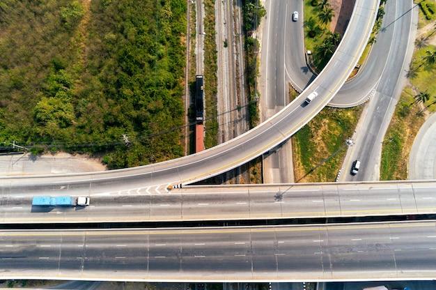 Vista aerea del carico camion e contenitore del treno sulla strada autostradale con auto, concetto di trasporto, importazione, esportazione industriale logistica trasporti trasporti terrestri sull'autostrada asfaltata