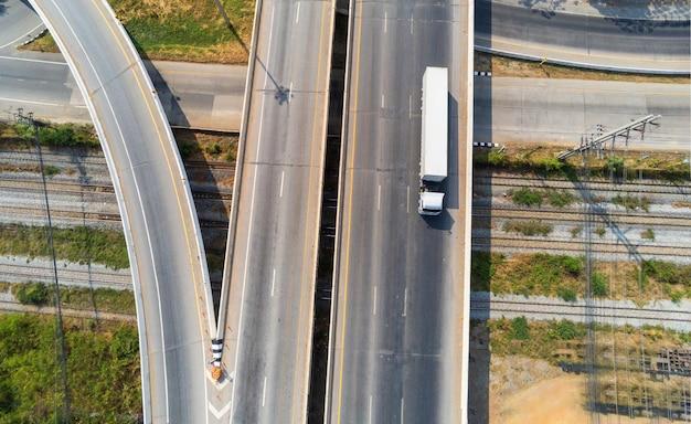 Vista aerea del carico bianco camion su strada autostrada con container, concetto di trasporto, importazione, esportazione logistica industriale trasporto trasporto terrestre sulla superstrada asfaltata
