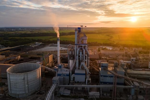 Vista aerea della torre della fabbrica di cemento con struttura dell'impianto in calcestruzzo alta nell'area di produzione industriale. produzione e concetto di industria globale.