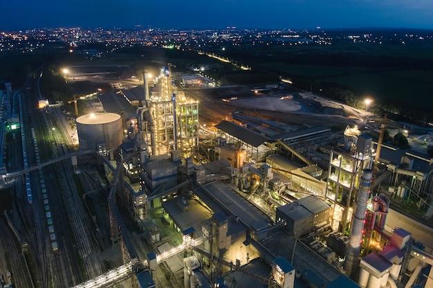 Vista aerea della fabbrica di cemento con struttura in calcestruzzo alta e gru a torre nell'area di produzione industriale di notte. produzione e concetto di industria globale.
