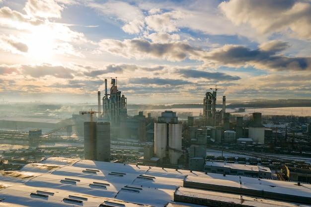 Vista aerea della cementeria con alta struttura di fabbrica e gru a torre nell'area di produzione industriale al tramonto.