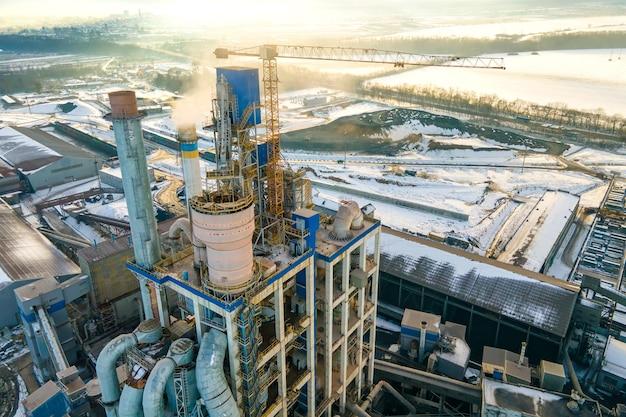 Vista aerea della cementeria con alta struttura di fabbrica e gru a torre nell'area di produzione industriale.