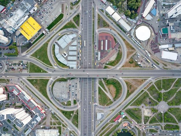 Vista aerea della città di kiev, un moderno incrocio stradale con auto, grattacieli, centri commerciali con parcheggi e aree verdi, distretto di poznyaki, ucraina. foto dal drone