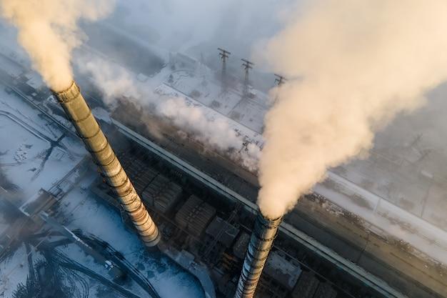 Vista aerea dei tubi alti della centrale elettrica del carbone con fumo nero che si alza atmosfera inquinante al tramonto.