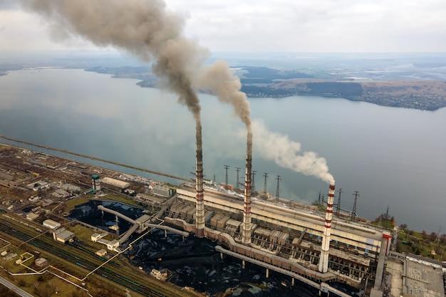 Vista aerea dei tubi alti della centrale elettrica del carbone con fumo nero che si alza in atmosfera inquinante.