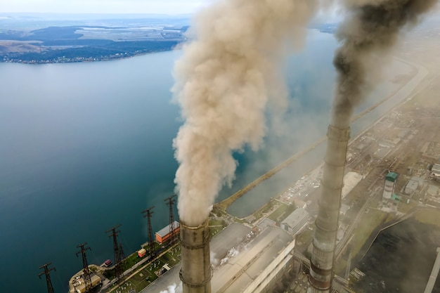 Vista aerea dei tubi alti della centrale elettrica a carbone con fumo nero che sale in atmosfera inquinante poll Foto Premium
