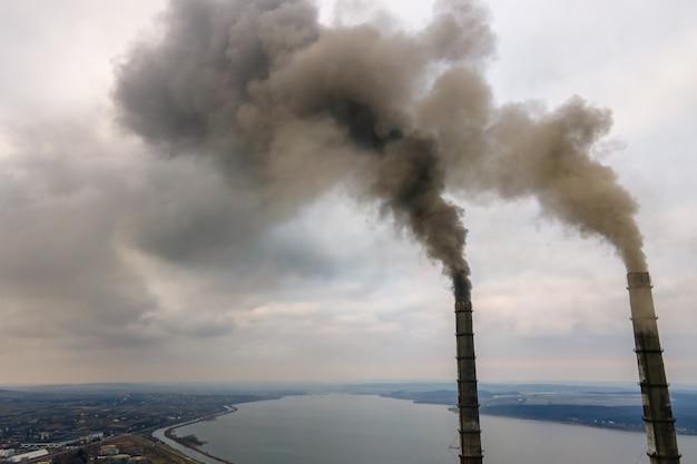 Vista aerea dei tubi alti della centrale elettrica del carbone con fumo nero che si alza atmosfera inquinante.
