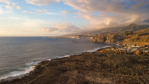 Vista aerea della costa e schiuma delle onde del mare, terreno asciutto e sentieri, isole canarie
