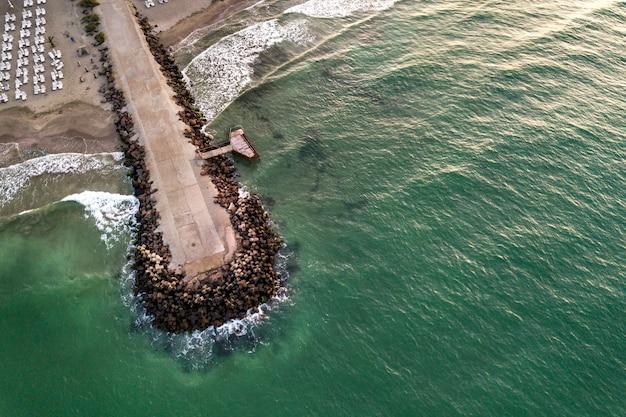 Vista aerea di un pilastro di cemento sulla riva del mare con pietre di rottura dell'onda