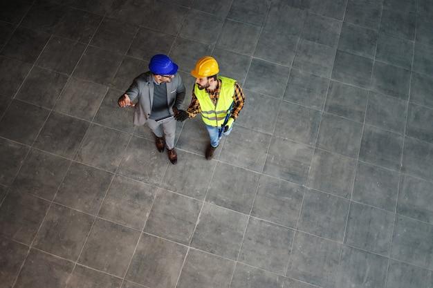 Vista aerea di operaio edile e architetto camminando sul cantiere e discutendo del progetto.