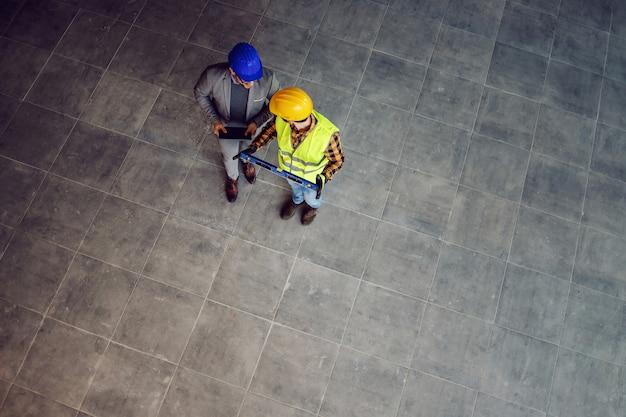 Vista aerea di operaio edile e architetto camminando sul cantiere e discutendo del progetto