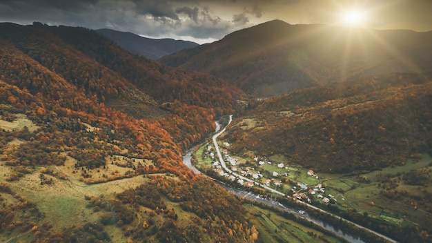 Vista aerea sul drammatico paesaggio al tramonto autunnale. piccolo villaggio di montagna nel canyon circondato da prati, colline arancioni, foreste di pini. carpazi, ucraina, europa. filtro tonificante vintage retrò scuro.
