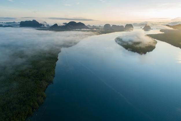 Colpo di drone vista aerea del bellissimo oceano contro il cielo al mattino nebbia nebbia alba drone sta sorvolando il mare e la foresta di mangrovie paesaggio veduta dall'alto ripresa aerea dinamica incredibile vista della natura.