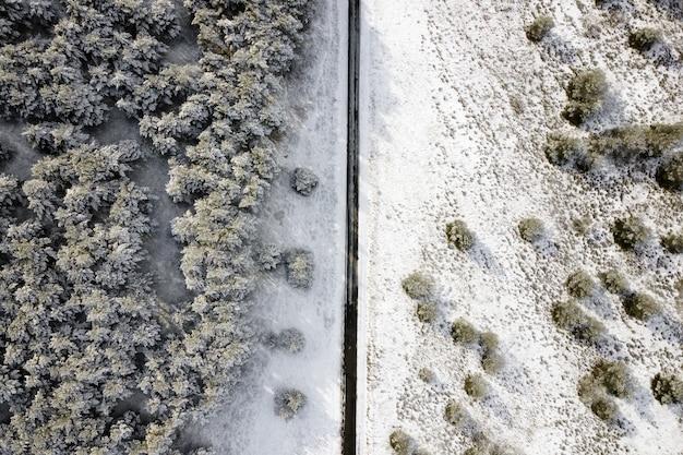 Vista aerea della strada innevata vuota nella foresta di inverno.