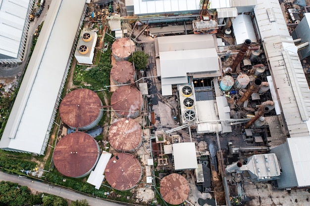 Vista aerea della fabbrica di lavorazione della raffineria di etanolo industriale o di biocarburante con fumo dal camino, serbatoi di stoccaggio e magazzino. problema di inquinamento climatico e riscaldamento globale
