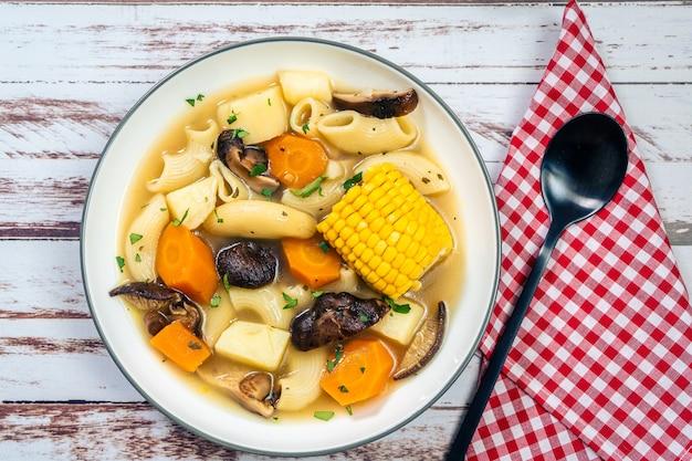 Vista aerea di una squisita zuppa fatta in casa di pollo, verdure e funghi con pasta e mais. servito in una ciotola su un tavolo in legno rustico. concetto di cibo naturale e sano