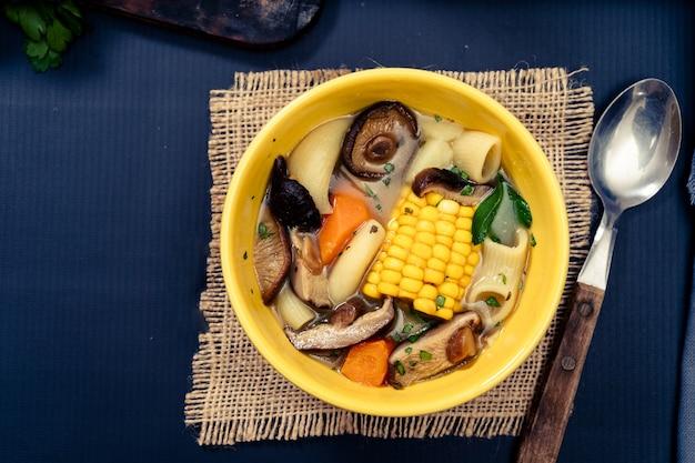 Vista aerea di una squisita zuppa fatta in casa di pollo, verdure e funghi con pasta e mais. servito in una ciotola su un tavolo con tovaglia blu. concetto di cibo naturale e sano