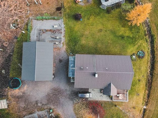 Fattoria vista aerea in mezzo alla foresta, trattore e fienili. foto scattata da un drone. finlandia, pornainen.