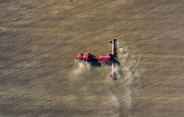 Vista aerea del contadino in un trattore che prepara la terra con un coltivatore di semina