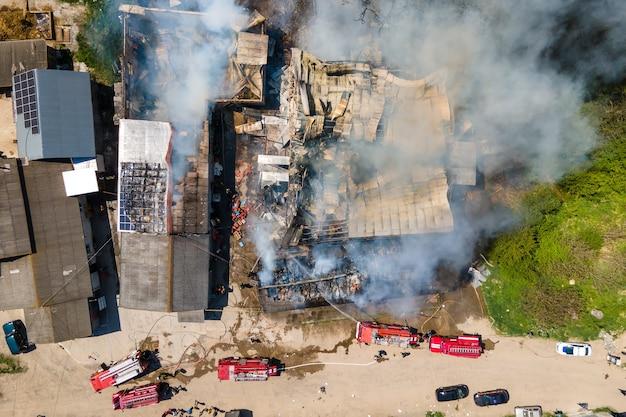 Vista aerea dei vigili del fuoco che estinguono l'edificio in rovina in fiamme con tetto crollato e fumo scuro in aumento.