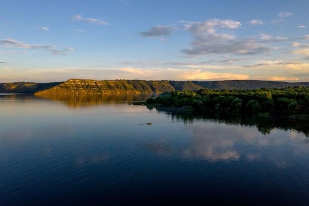 Vista aerea del pescatore alla barca sul fiume dorato del tramonto. sagoma di pescatori con la sua barca