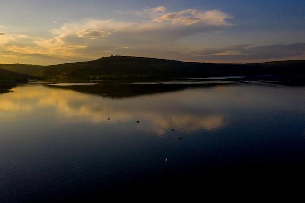 Vista aerea del pescatore alla barca sul fiume dorato del tramonto