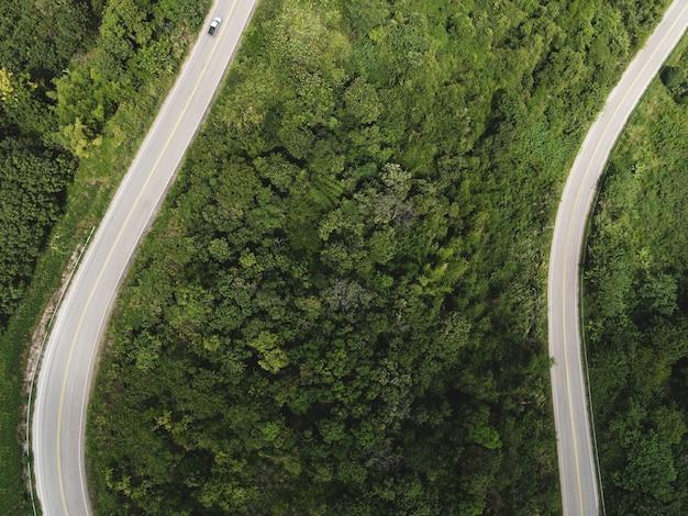 Vista aerea della natura della foresta con auto sulla strada sull'albero verde di montagna, curva stradale vista dall'alto dall'alto, vista a volo d'uccello strada attraverso la montagna la foresta verde bellissimo ambiente fresco
