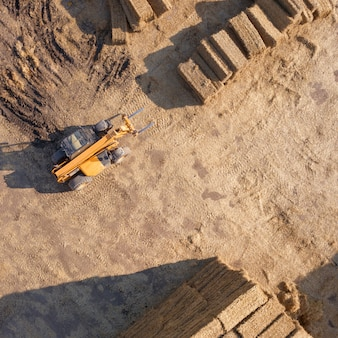 Vista aerea da drone grandi pile di balle di fieno secco nel campo. il trattore piega le balle di fieno in una giornata di sole. vendemmia autunnale. vista dall'alto